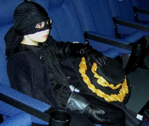 Small boy dressed as Zorro sits in the movie theatre seat.