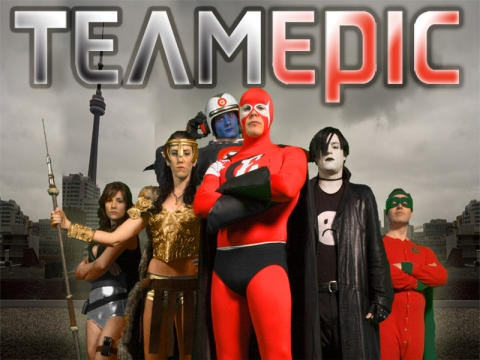 The cast of Team Epic superheroes posre in front of a skyline including the CN Tower.