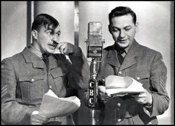 Johnny Wayne holds a brush under his nose to compliment his Hitler Hairdo as Frank Shuster reads from the script at a CBC microphone