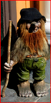 European troll with a walking stick stands on a city street.