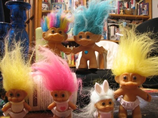 a naked rainbow haired troll doll, a naked blue haired troll doll with blue gem inset at navel, yellow haired and pink haired baby trolls wearing bibs and nappys, a white haired baby troll in a bunny suit, and a yellow haired troll wearing balloon trunks